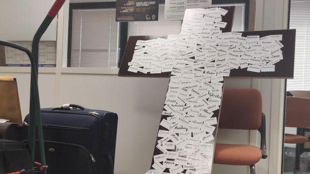 Au milieu des bagages prêts à partr pour Lourdes, la grande croix portant les noms des pèlerins qui vont rester en Ille-et-Vilaine