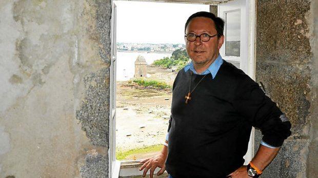 Le Père Olivier Roy près d'une fenêtre qui donne sur Solidor